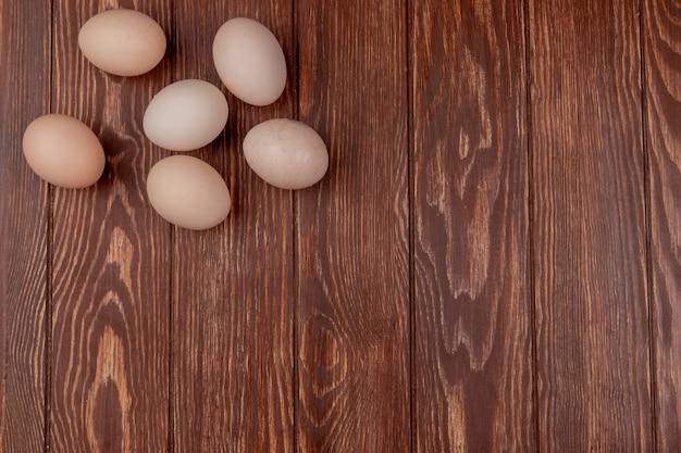 Bovenaanzicht van verse en ovale eieren op een houten achtergrond met kopie ruimte
