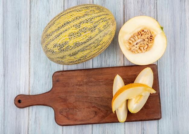 Bovenaanzicht van verse en rijpe plakjes meloen op houten keukenbord met meloenen op grijs hout