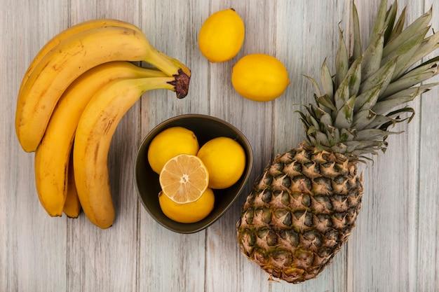 Bovenaanzicht van verse en sappige citroenen op een kom met ananas, bananen en citroenen geïsoleerd op een grijze houten oppervlak