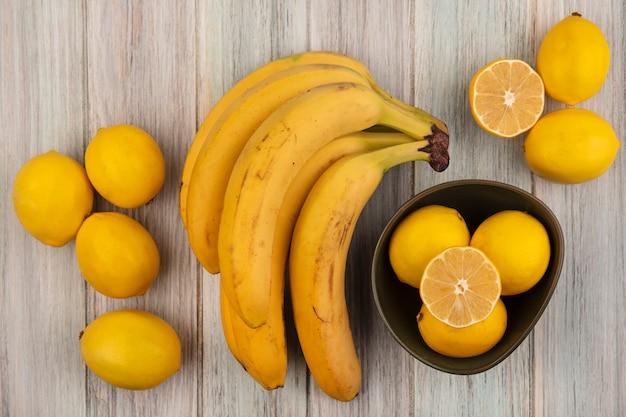 Bovenaanzicht van verse en sappige citroenen op een kom met bananen en citroenen geïsoleerd op een grijze houten muur
