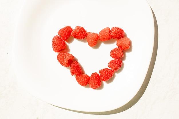Bovenaanzicht van verse en sappige frambozen in de vorm van een hart op witte keramische schotel. begrip liefde. sappig frambozendessert.