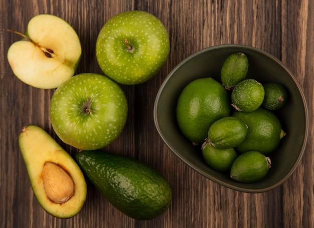 Bovenaanzicht van verse feijoas met limoenen (lemmetjes) op een kom met groene appels en avocado's geïsoleerd op een houten oppervlak