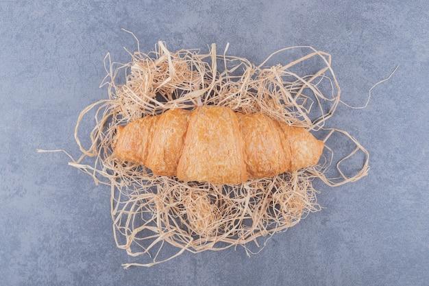 Bovenaanzicht van verse franse croissant op decoratief stro over grijze achtergrond.