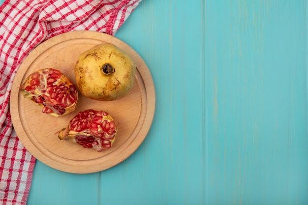 Bovenaanzicht van verse gehalveerde en hele granaatappels op een houten keukenbord op een gecontroleerde doek op een blauwe houten muur met kopie ruimte
