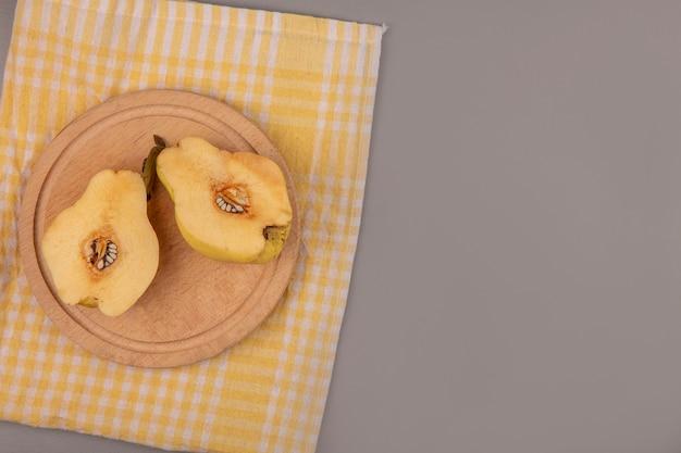 Bovenaanzicht van verse gehalveerde kweeperen op een houten keukenbord op een geel geruit doek met kopie ruimte