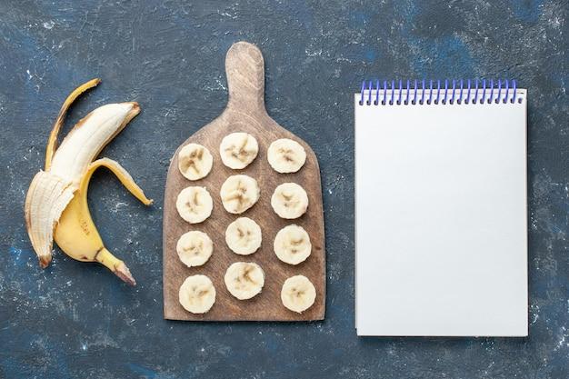 Bovenaanzicht van verse gele banaan zoet en heerlijk gepeld en in plakjes gesneden met blocnote op donker bureau, fruitbes zoet vitamine gezondheid