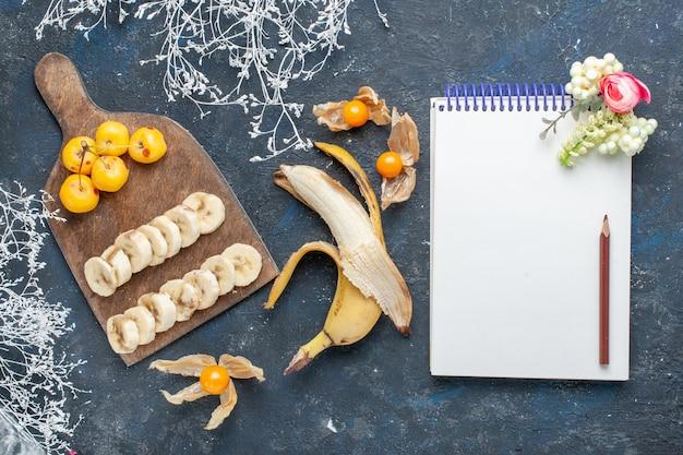 Bovenaanzicht van verse gele banaan zoet en lekker gesneden met kladblok zoete kersen op donker, fruit bes zoete vitamine gezondheid