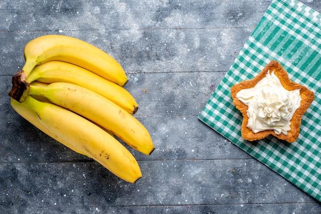 Bovenaanzicht van verse gele bananen hele bessen met cake op grijs, fruit bessen vitaminesmaak