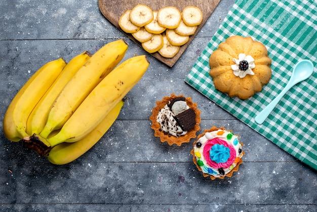 Bovenaanzicht van verse gele bananen hele bessen met taarten op grijs, fruitbes vitaminesmaak