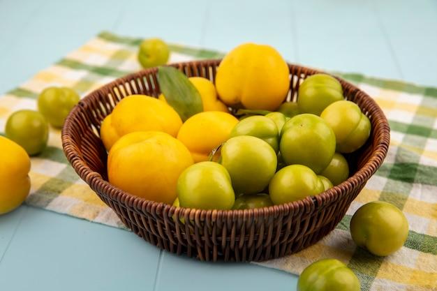 Bovenaanzicht van verse gele perziken op een emmer met groene kersenpruimen op een gecontroleerde doek op een blauwe achtergrond
