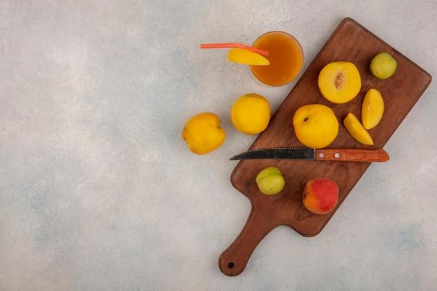 Bovenaanzicht van verse gele perziken op een houten keukenbord met mes met groene kersenpruimen met vers perziksap op een witte achtergrond met kopie ruimte