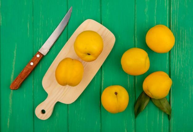 Bovenaanzicht van verse gele perziken op een houten keukenbord met mes op een groene houten achtergrond