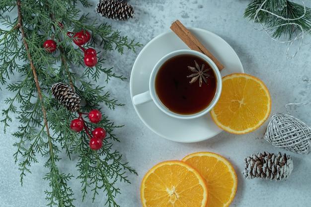 Bovenaanzicht van verse geurige thee met stukjes sinaasappel, kerstconcept.