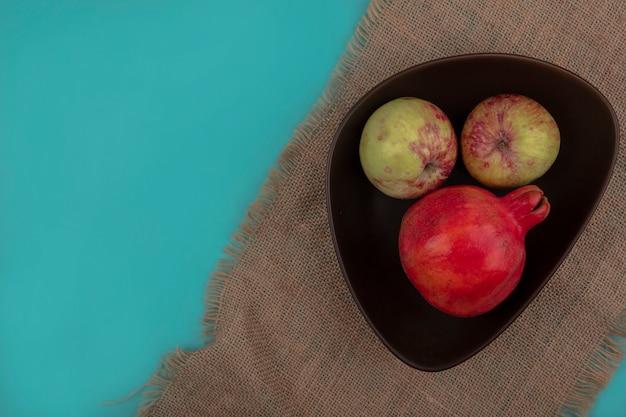 Bovenaanzicht van verse granaatappel met appels op een kom op een zakdoek op een blauwe achtergrond met kopie ruimte