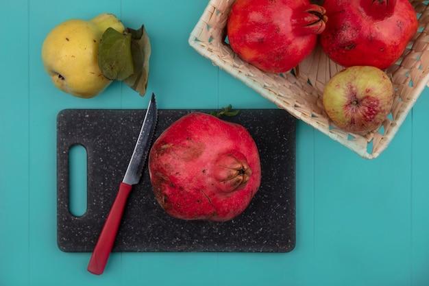 Bovenaanzicht van verse granaatappel op een bord van de zwarte keuken met mes met een emmer fruit op een blauwe achtergrond