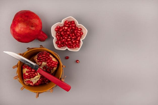 Bovenaanzicht van verse granaatappel op een emmer met mes met granaatappelpitjes op een kom met kopie ruimte
