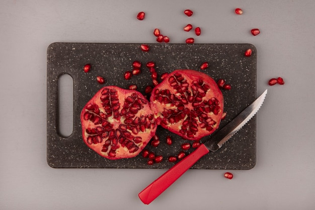 Bovenaanzicht van verse granaatappels op een bord met zwarte keuken met mes Gratis Foto