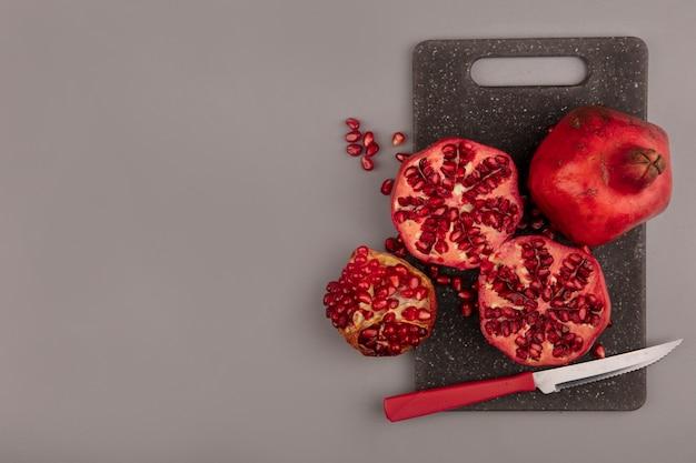 Bovenaanzicht van verse granaatappels op een bord van de zwarte keuken met mes met kopie ruimte