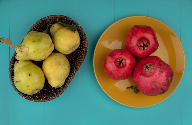 Bovenaanzicht van verse granaatappels op een gele plaat met kweeperen op een emmer op een blauwe achtergrond