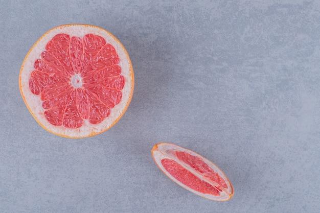 Bovenaanzicht van verse grapefruit op grijze ondergrond