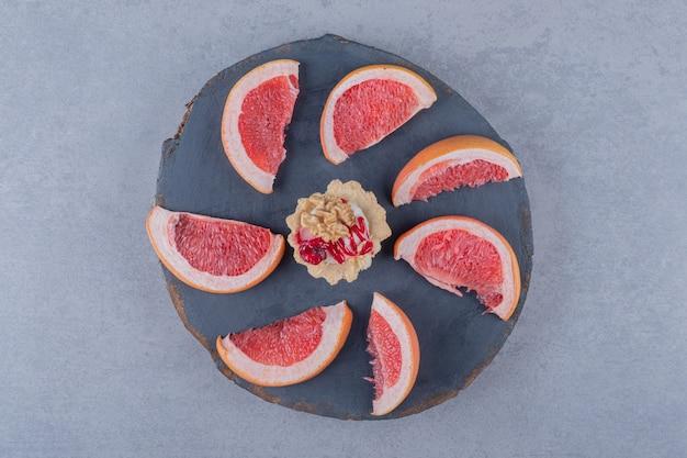 Bovenaanzicht van verse grapefruit plakjes op een houten bord