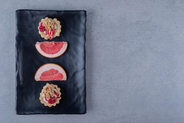 Bovenaanzicht van verse grapefruitplakken met koekje op zwarte plaat