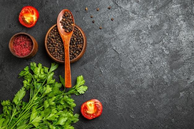 Bovenaanzicht van verse greens met peper en tomaten op een grijze ondergrond