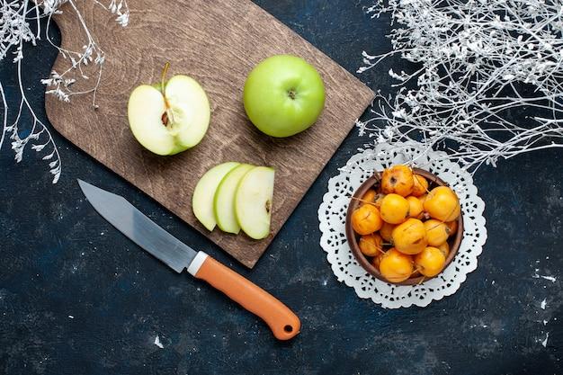 Bovenaanzicht van verse groene appels met zoete, zachte kersen op donkerblauw bureau, fruitmellow voedsel vitamine