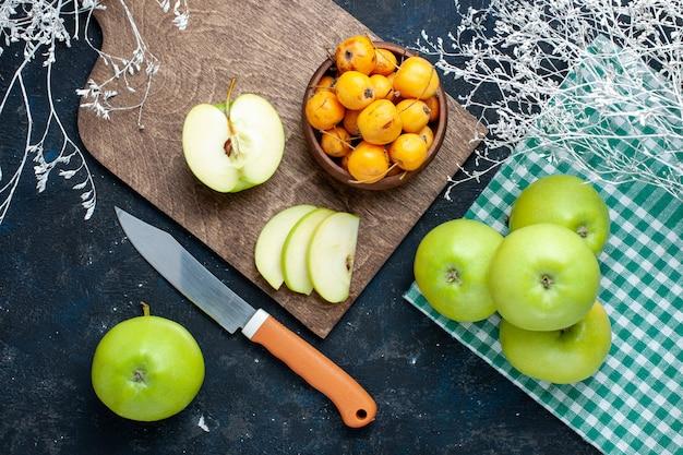 Bovenaanzicht van verse groene appels met zoete zachte kersen op donkere vloerfruit vers zacht