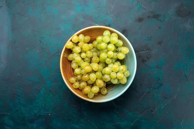 Bovenaanzicht van verse groene druiven in bruine plaat op donkere, verse druivenfruit