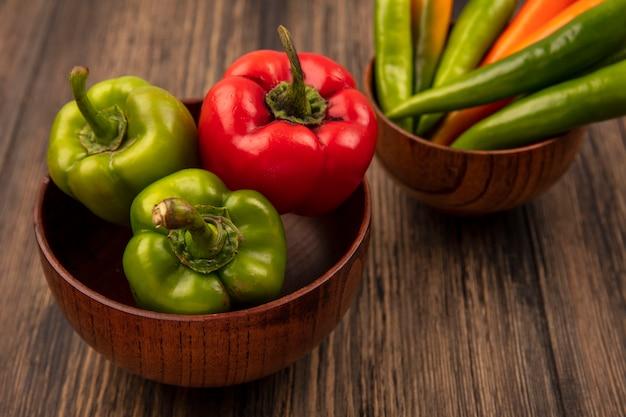 Bovenaanzicht van verse groene en rode paprika op een houten kom op een houten oppervlak