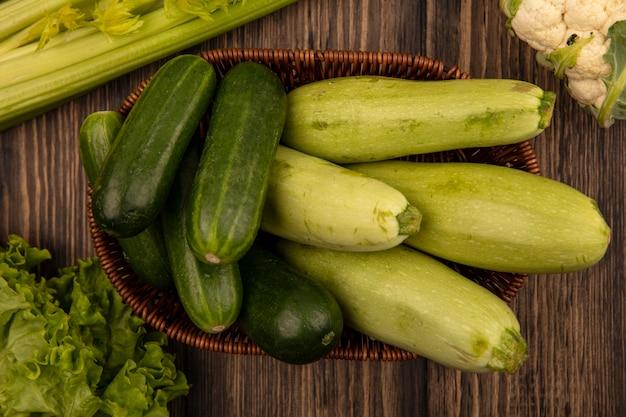 Bovenaanzicht van verse groene groenten zoals courgettes en komkommers op een emmer met sla, selderij en bloemkool geïsoleerd op een houten muur