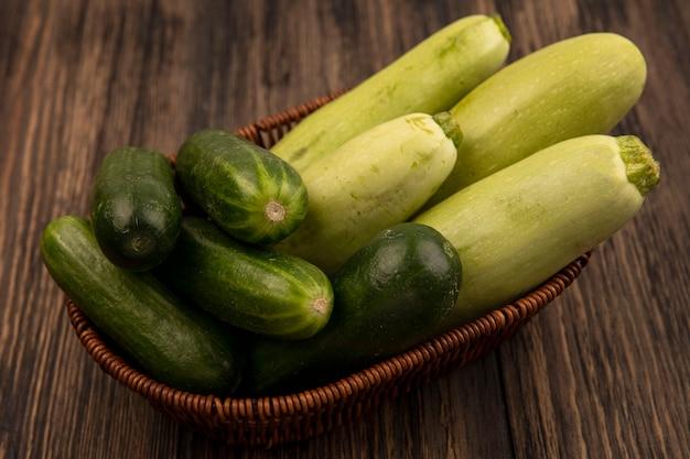 Bovenaanzicht van verse groene groenten zoals courgettes en komkommers op een emmer op een houten ondergrond