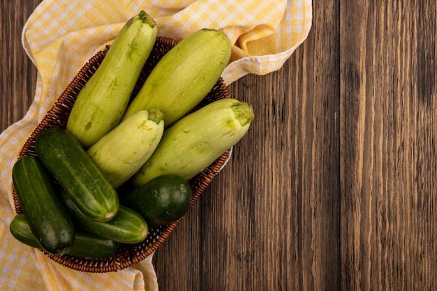 Bovenaanzicht van verse groene groenten zoals komkommers en courgettes op een emmer op een geel geruit doek op een houten oppervlak met kopie ruimte