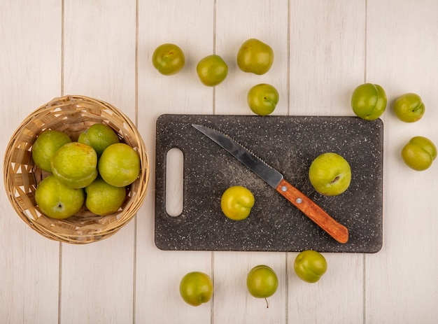 Bovenaanzicht van verse groene kersenpruimen op een snijplank van de keuken met mes met kersenpruimen op een emmer op een witte houten achtergrond