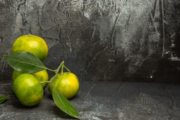 Bovenaanzicht van verse groene mandarijnen met bladeren aan de rechterkant van grijze achtergrondbeelden