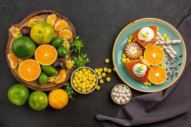 Bovenaanzicht van verse groene mandarijnen met feijoa's en plakjes cake op dark