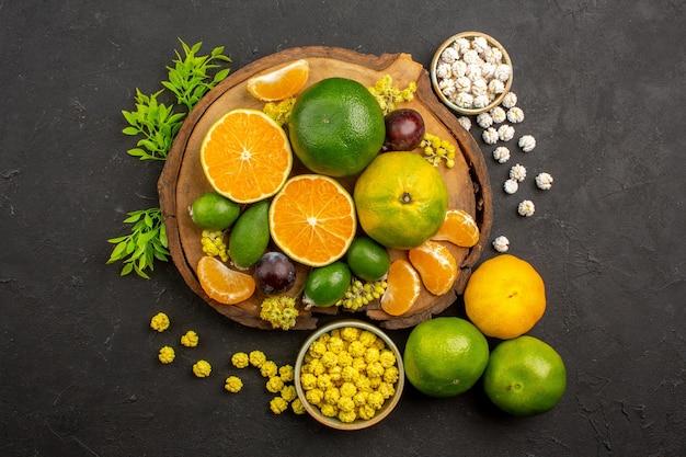 Bovenaanzicht van verse groene mandarijnen met feijoa's en snoepjes op dark