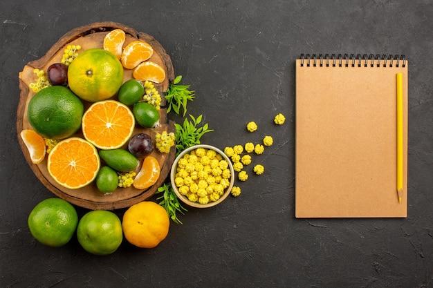 Bovenaanzicht van verse groene mandarijnen met feijoa's op donkere tafel