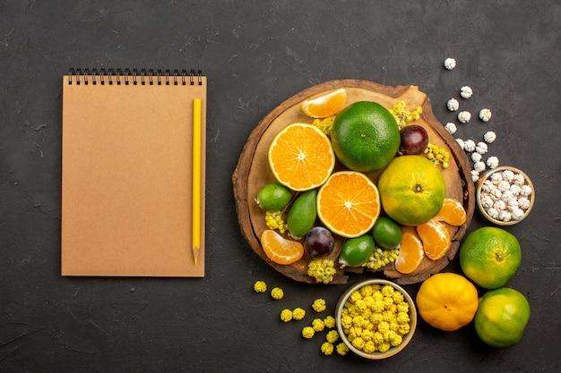Bovenaanzicht van verse groene mandarijnen met feijoa's op donkergrijs
