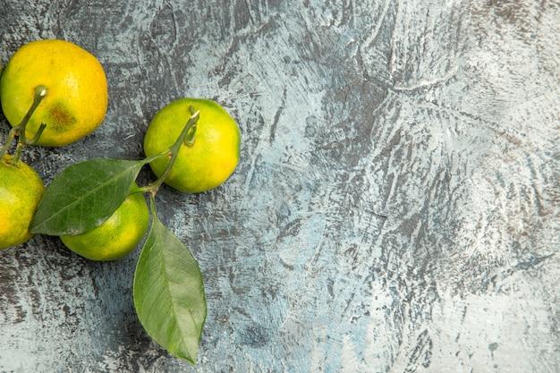 Bovenaanzicht van verse groene mandarijnen op grijze achtergrond