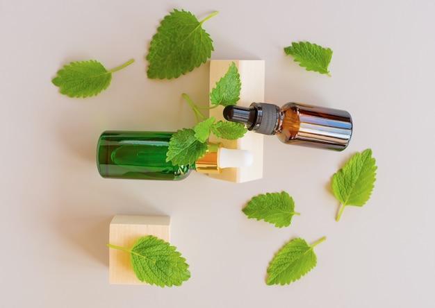 Bovenaanzicht van verse groene munt of groene muntblaadjes en glazen druppelflesjes etherische olie van munt op grijze achtergrond. natuurlijke kruiden medische aromatische plant concept.