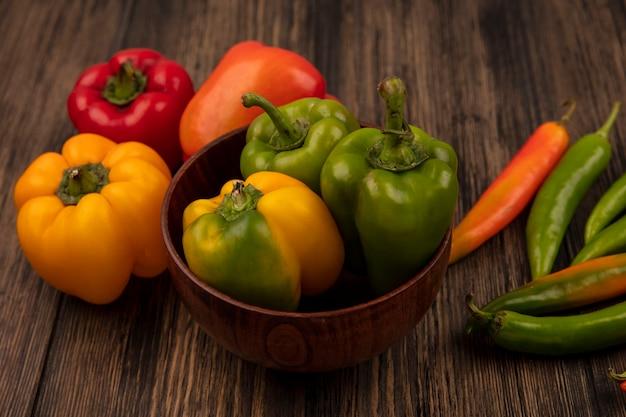 Bovenaanzicht van verse groene paprika's op een kom met kleurrijke paprika's geïsoleerd op een houten oppervlak