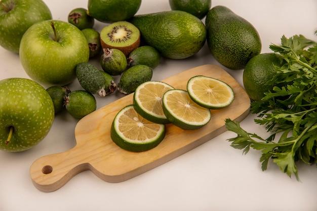 Bovenaanzicht van verse groene plakjes limoenen op een houten keukenbord met groene appels, kiwi en avocado's geïsoleerd op een witte achtergrond