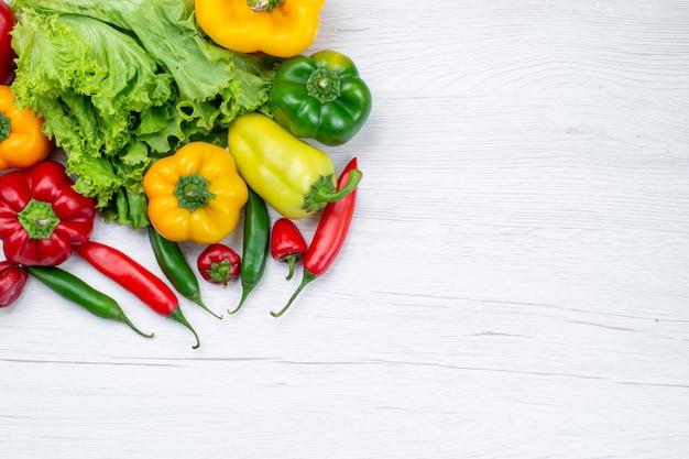 Bovenaanzicht van verse groene salade samen met paprika en pittige paprika op licht bureau, plantaardig voedselingrediënt