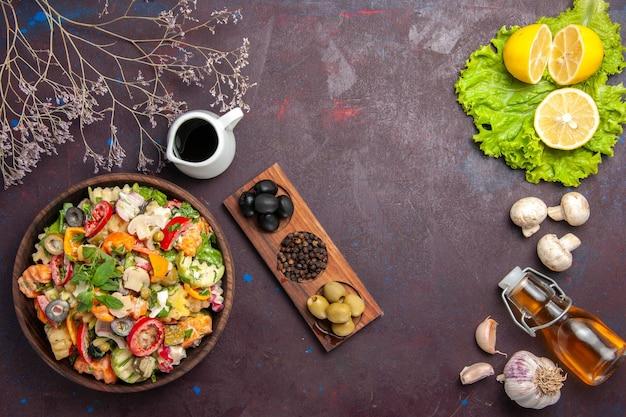 Bovenaanzicht van verse groente. salade met olijven en schijfjes citroen op zwart