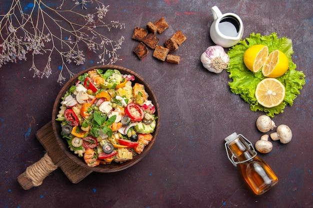 Bovenaanzicht van verse groente. salade met schijfjes citroen en groene salade op zwart