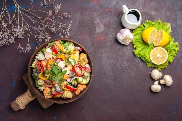 Bovenaanzicht van verse groente. salade met schijfjes citroen en groene salade op zwarte tafel