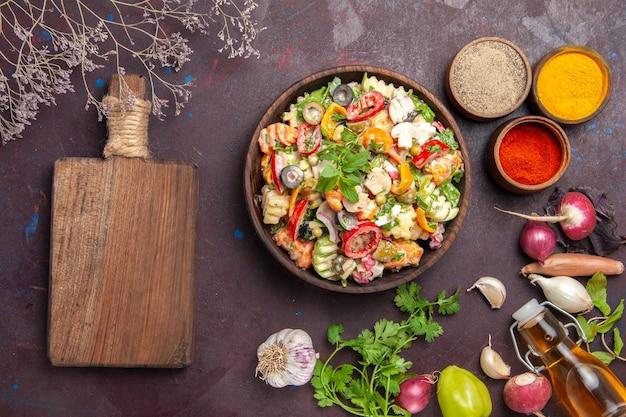 Bovenaanzicht van verse groente. salade met verschillende kruiden op zwart