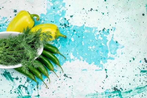 Bovenaanzicht van verse groenten binnen plaat met groene paprika en pittige paprika's op helderblauwe, groene bladgroente productmeel